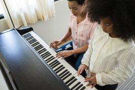 American African mom and daughter playing piano at home