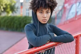 Cropped shot of serious dark skinned woman hipster has curly hair, dressed in sweatshirt with hoodie, leans at fence, spends free time on playground, enjoys leisure waits for friend to play basketball