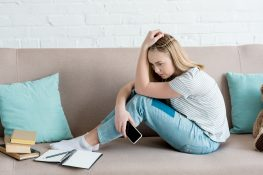 depressed teen girl sitting on couch with smartphone while doing homework