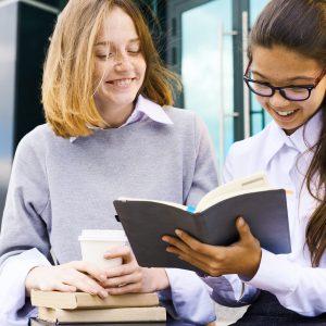 Schoolgirls Reading Book Outdoors