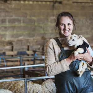 Woman standing in a barn, holding a newborn lamb dressed in a knitted jumper.,Farming,UK