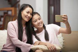 Adult woman with teenage daughter taking selfie