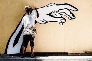 activist and artist Corie Mattie painting a wall